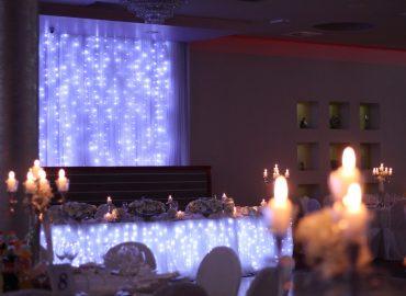 ukrašeni stol za mladence u sali za svadbe Velika dvorana u restoranu Taverna Kraljevec izdaleka slikano s bijelim lampicama