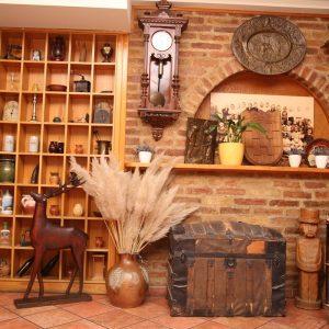 ukrasi na zidu, vino, antikni sat, antikna skrinja, kamin, jelen u sali Restoran restorana Taverna Kraljevec